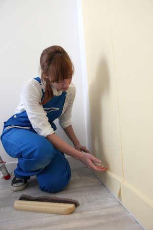 Female decorator hanging wallpaper photo
