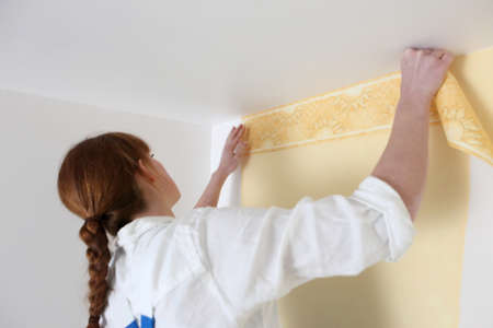 Woman putting up wallpaper photo