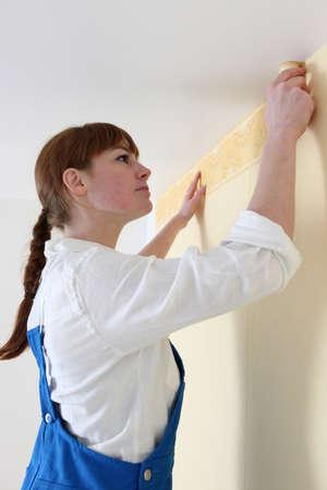 gluing: Woman gluing wallpaper border