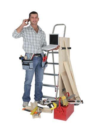 Carpenter stood with equipment making telephoning customer photo
