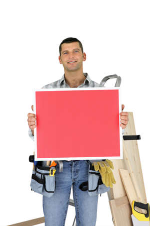 Builder holding red message board photo