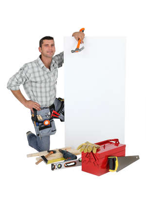 Handyman with a board left blank for your message photo
