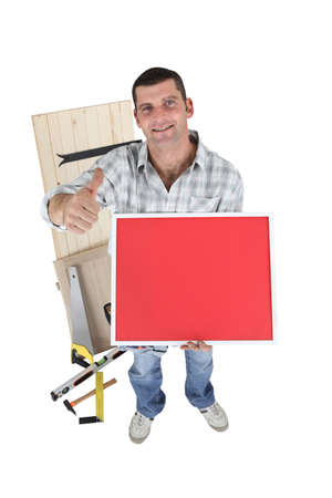 Handyman holding a red sign Stock Photo - 13778920