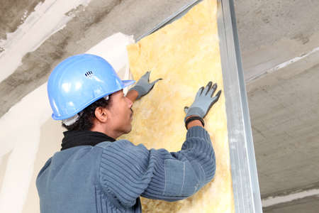 fiberglass: Man fitting wall insulation