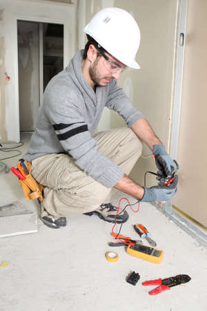 Man snipping wall wiring Stock Photo - 13780620