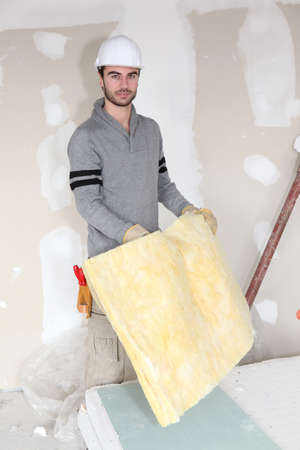 plasterboard: Worker handling square of insulation