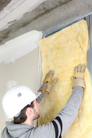 rafter: Man attaching insulation to wall