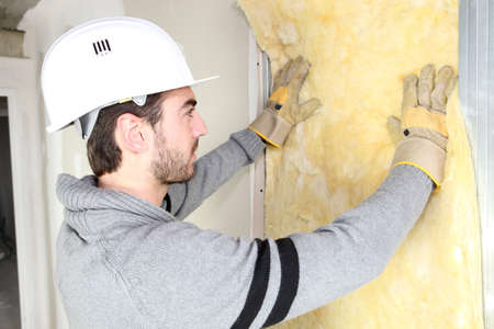 insulation: Man installing wall insulation
