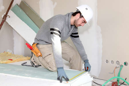knee bend: Bricklayer measuring plasterboard Stock Photo