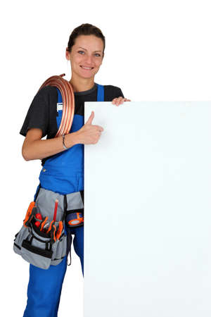 Female plumber with a board left blank for your message photo
