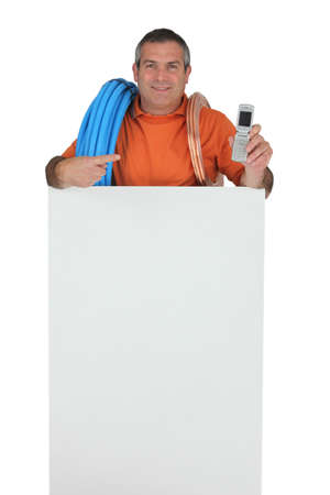 indicating: Plumber with a telephone