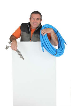 flexi: Plumber with materials and a board left blank for your message Stock Photo