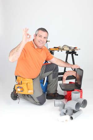 plumber kneeling with laptop photo
