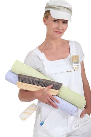 Female decorator holding rolls of wallpaper photo