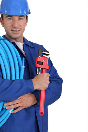 flexi: Closeup of an electrician with roll of blue cable and a wrench