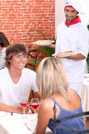 pizza maker: Young couple eating out in a pizzeria