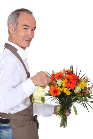 median age: Florist spraying flowers