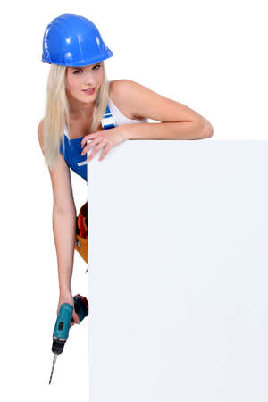 Woman stood hedind white panel with drill Stock Photo - 13782330