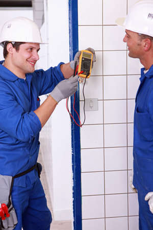 wireman: Two young plumbers larking about with a voltmeter Stock Photo