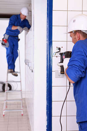 Tradesman using an electric screwdriver photo