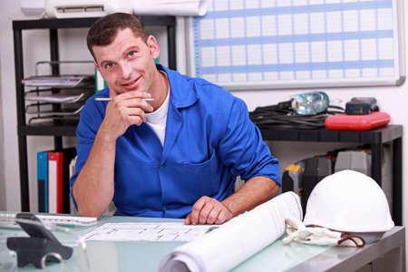 building planners: Manual worker looking at paperwork