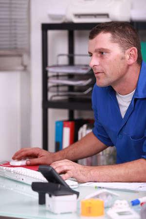 artesano: Plomero utilizando una computadora de escritorio