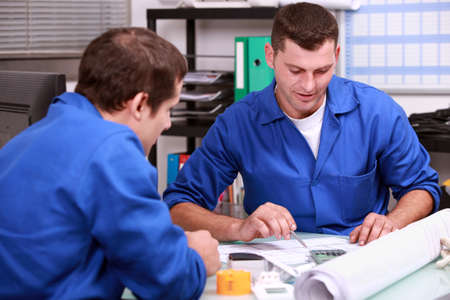 assiduous: Skilled tradesmen examining a blueprint Stock Photo