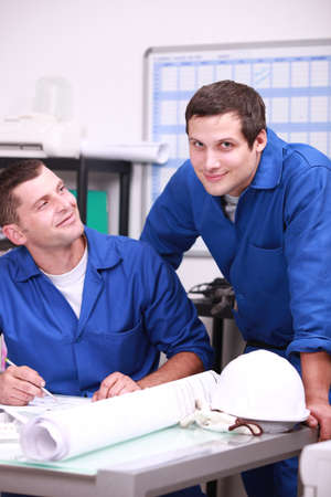 Two factory workers in the office checking stock photo
