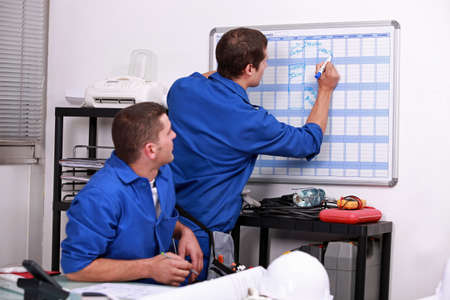 Manual workers writing on a calendar photo