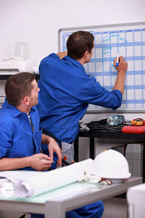 day planner: Laborers in office planning appointments Stock Photo