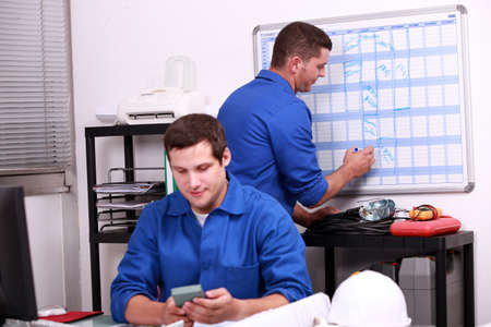 hard sell: Two electricians working in back office Stock Photo