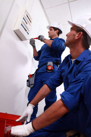 mechanical energy: Electricians installing circuit breaker Stock Photo