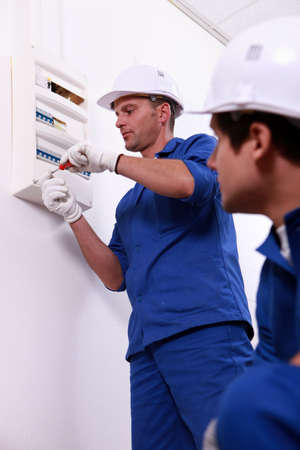 Tradesman repairing a distribution board photo