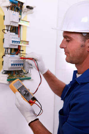Electrician inspecting fuse box photo
