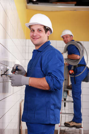 Electricians working in a tiled room photo