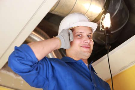 ventilation: Manual worker inspecting air-conditioning system Stock Photo