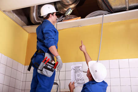 conditioning: two technicians checking the air conditioning in the ceiling Stock Photo