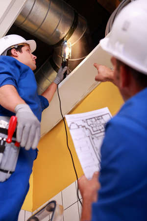 Ventilation: Two workers inspecting ventilation system Stock Photo
