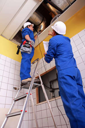 Man and woman repairing ventilation system photo