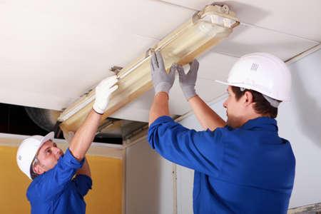 Dos electricistas reparación de la iluminación de oficinas
