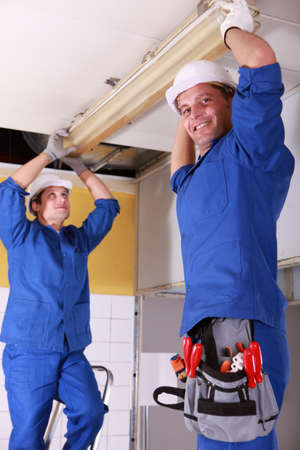 Electricians installing neon on ceiling Stock Photo - 13782800
