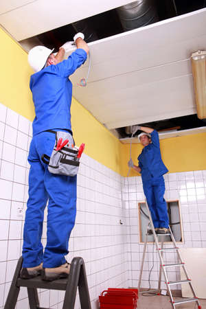 commercial construction: Electrician wiring a large tiled room Stock Photo