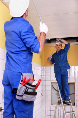 Electricians wiring a large room photo