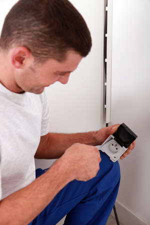 jumpsuite: handyman looking an electrical outlet