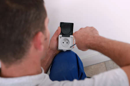 electrician repairing an electricity socket photo