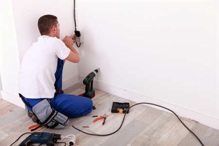 bare wire: Electrician repairing wiring