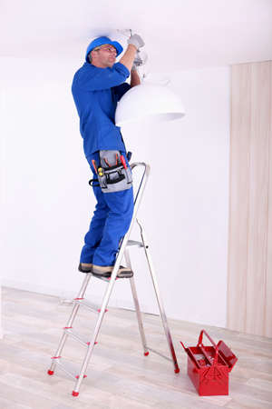 Electrician hanging a ceiling light photo