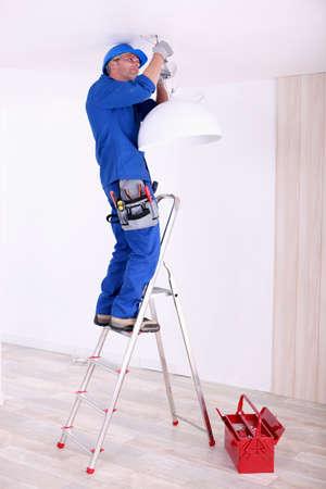 electricidad industrial: Electricista que cuelga una lámpara de techo Foto de archivo
