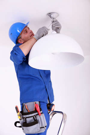 light fitting: Electrician fitting a ceiling light