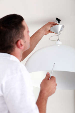 fixate: handyman fixate a lamp on the ceiling Stock Photo